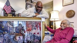 SUFFOLK NATIVE AND artist Timothy Giles presents a painting he created to Dr. Olivia Hooker, one of the last survivors of the 1921 Tulsa Race Riot. (Photo by Suffolk News-Herald)